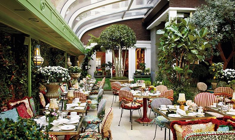 Στον εσωτερικό κήπο με άρωμα άνοιξης από συκιές και πορτοκαλιές και μία συρόμενη γυάλινη στέγη σερβίρεται μεταξύ άλλων και πρωινό σε υπέροχες πορσελάνες με ζωηρά χρώματα και ασημένια μαχαιροπίρουνα