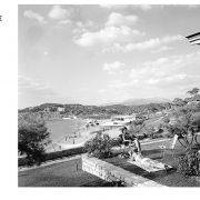 Στο λεύκωμα ξεδιπλώνεται με στοιχεία και μαρτυρίες η ιστορία του ξενοδοχειακού συγκροτήματος. Στη φωτογραφία: ένοικοι καμπάνας χαλαρώνουν στο γκαζόν με θέα τη θάλασσα, 1961