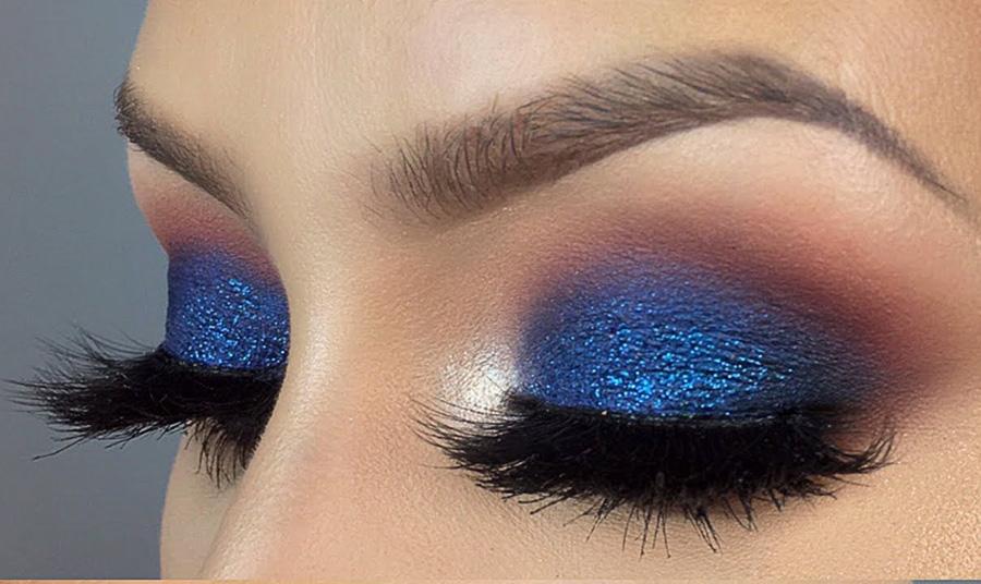 Χρησιμοποιήστε μία μπλε σκούρα ή έντονη σκιά όπως η navy blue ή η μωβ-μπλε για ένα ιδιαίτερο και καλοκαιρινό smokey. Για λάμψη, εφαρμόστε σκιά με γκλίτερ