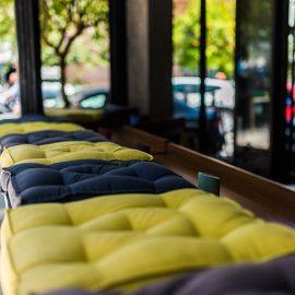 Τα άνετα ανοιχτόχρωμα ξύλινα έπιπλα με τα χαρούμενα, πολύχρωμα μαξιλάρια σας προσκαλούν να καθίσετε αναπαυτικά και να απολαύσετε το κρασί και το φαγητό σας