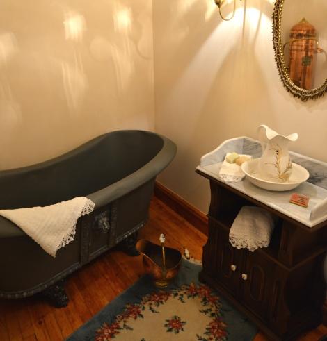 Το μπάνιο του σπιτιού με το πορσελάνινο λαβομάνο και τις κεντητές λευκές πετσέτες
