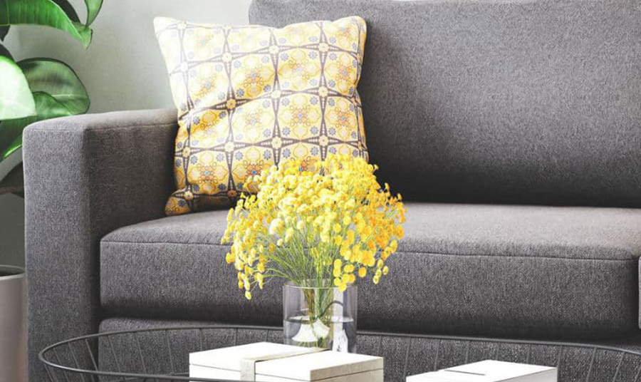 'Ένα μαξιλάρι ή ένα μπουκέτο κίτρινα λουλούδια λειτουργούν σαν αχτίδες του ήλιου σε ένα μουντό γκρι καναπέ