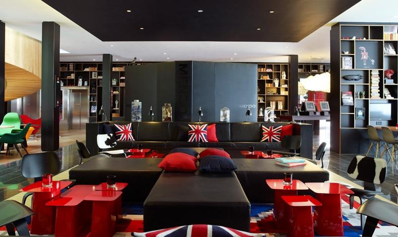 Σε μια άλλη γωνιά, τα κατακόκκινα τραπεζάκια των Γάλλων Ronan & Erwan Bouroullec ζωντανεύουν τον χώρο και συνδυάζονται με τα χρώματα της βρετανικής σημαίας στα μαξιλάρια