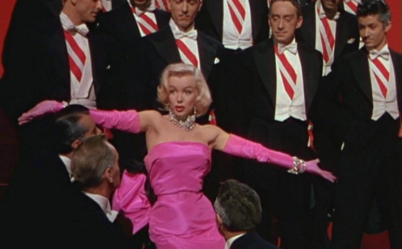 Σκηνή από την ταινία «Μερικοί το προτιμούν καυτό» και η λαμπερή Μέριλιν αστράφτει στη ροζ σατέν τουαλέτα και τα εντυπωσιακά διαμαντένια κοσμήματα