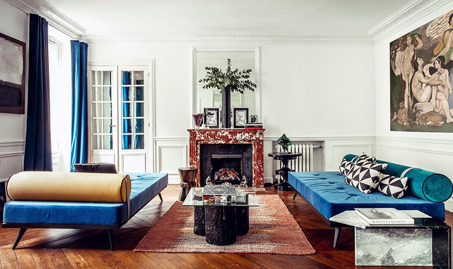 Τα ρετρό ανάκλιντρα πλαισιώνουν το αρθρωτό τραπεζάκι σαλονιού στον χώρο υποδοχής. Οι μπλε βελούδινες κουρτίνες ισορροπούν την απόχρωση του ζαφειριού στα ανάκλιντρα με τον λαμπερό λευκό στους τοίχους και το ταβάνι