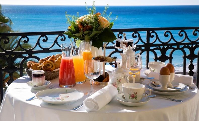 Οι τυχεροί θαμώνες του απολαμβάνουν ένα θεσπέσιο πρωινό στο μπαλκόνι, με θέα τη μεσογειακή θάλασσα
