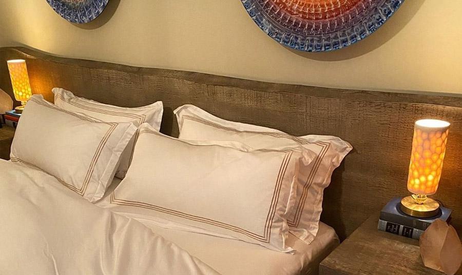 Ένα ξύλινο κεφαλάρι «μεταφέρει» μία φυσική νότα στο υπνοδωμάτιο, σε συνδυασμό με ιδιαίτερα ανατολίτικης αισθητικής διακοσμητικά στον τοίχο και   ουδέτερα κλινοσκεπάσματα