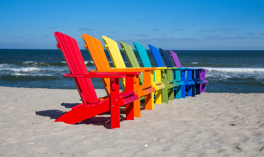 Πολύχρωμες πολυθρόνες Adirondack σε μία παραλία…