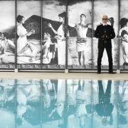 O Καρλ Λάγκερφελντ φωτογραφημένος στην εσωτερική πισίνα του Le Metropole στο Μόντε Κάρλο με τις σκηνές από την ελληνική μυθολογία να κοσμούν τον περίγυρο