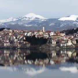 Η πόλη καθρεφτίζεται στα παγωμένα νερά της λίμνης και στο βάθος οι χιονισμένες βουνοκορφές