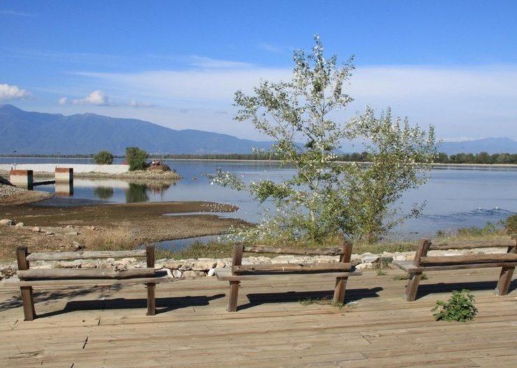 Ξύλινα παγκάκια μπροστά στη γαλήνια ατμόσφαιρα της λίμνης Κερκίνη