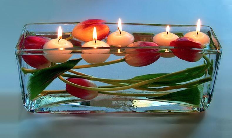 Ένα παραλληλόγραμμο βάζο, τουλίπες και επιπλέοντα κεριά. Μπορείτε να χρησιμοποιήσετε κεριά στα ίδια χρώματα με τα λουλούδια