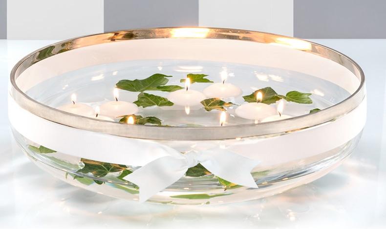 Λευκά κεριά, λευκή κορδέλα δεμένη γύρω από το φαρδύ μπολ και απλά πράσινα φύλλα στο νερό