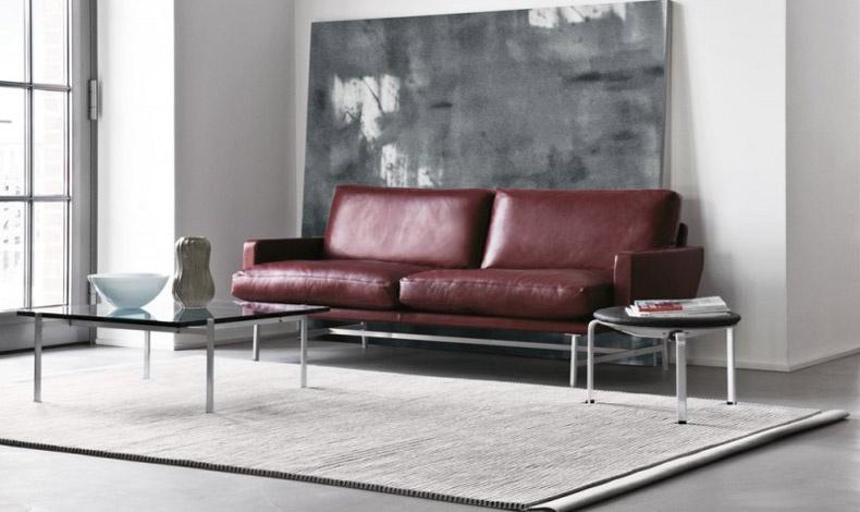 Σε φόντο γκρι και λευκό, η έμφαση δίνεται από τον δερμάτινο καναπέ στην απόχρωση Marsala