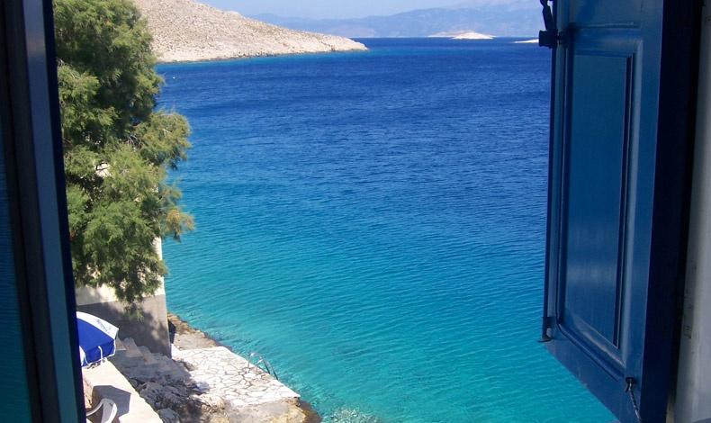 Το παράθυρο με τα γαλάζια παραθυρόφυλλα, το σιδερένιο μπαλκόνι με θέα στη θάλασσα του ονείρου που σου θυμίζει γιατί είναι ευτυχία να ζεις στη Μεσόγειο