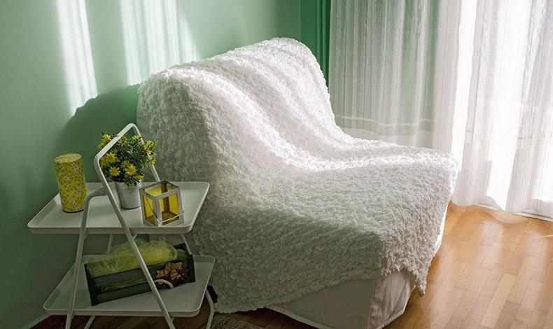 Η πολυθρόνα που μετατρέπεται σε μονό κρεβάτι με μία κίνηση στο δεύτερο δωμάτιο του διαμερίσματος με δικό του μπαλκόνι που βλέπει σε κατάφυτο κήπο