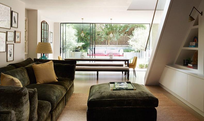 Το κομψό καθιστικό με τα μεγάλα ανοίγματα που φωτίζουν το σπίτι «βλέπει» σε έναν καταπράσινο κήπο