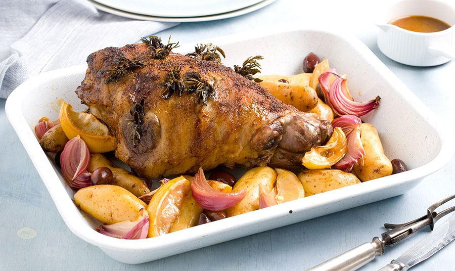 Μπούτι αρνιού με μυρωδικά, πατάτες και κρεμμύδια