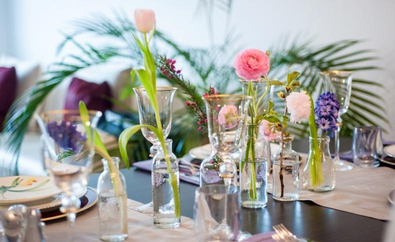 Διαφορετικά μεγέθη και σχήματα μπουκαλιών με λίγα λουλούδια στο καθένα είναι η νέα τάση στο ντεκόρ του τραπεζιού