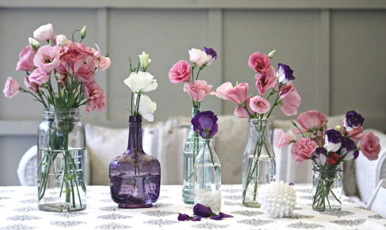 Χρησιμοποιήστε γυάλινα μπουκάλια σε διάφορα σχήματα και ύψη και βάλτε λίγα λουλούδια στο καθένα. Είναι μία ιδέα για να στολίσετε το κέντρο ενός τραπεζιού ή μίας κονσόλας