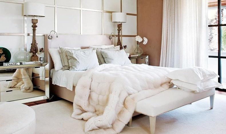 Μία κρεβατοκάμαρα με λευκό και στοιχεία γήινα και χρυσαφί δίνει τόνο πολυτέλειας που ενισχύεται με μία λευκή γούνα ριγμένη στο κρεβάτι που είναι και πολύ της μόδας